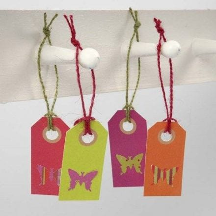 Un papillon perforé à partir de papier design et collé sur une étiquette