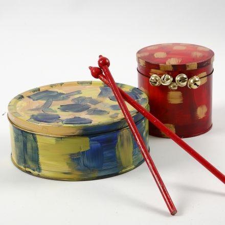 Un tambour fait à partir d'une boîte à gateaux et des baguettes faites avec des tuteurs