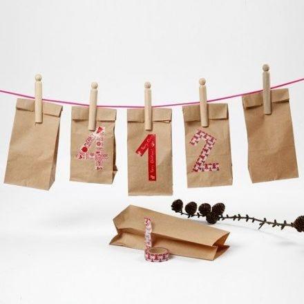 Un calendrier fait à partir de sacs en papier avec des cnuméros en ruban adhésif de masquage