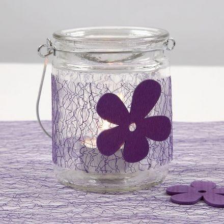 Un bougeoir avec une ceinture de filet violette et une fleur en bois