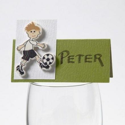 Un autocollant de footballeur en bois vernis sur un marque-place de la collection Happy Moments