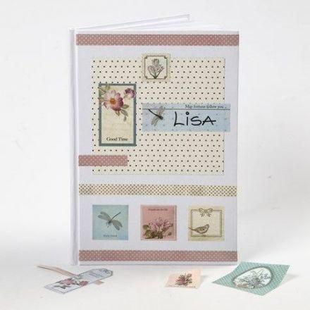 Des autocollants découpage et du papier Design sur la couverture d'un cahier de notes blanc