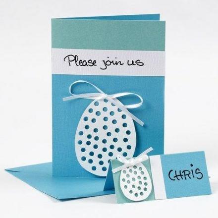 Une carte de vœux avec un œuf fait en papier cartonné et décoré d'un nœud en ruban