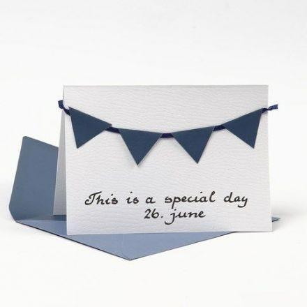 Une carte de vœux et une enveloppe décorées avec une guirlande bleue faite dans du papier martelé