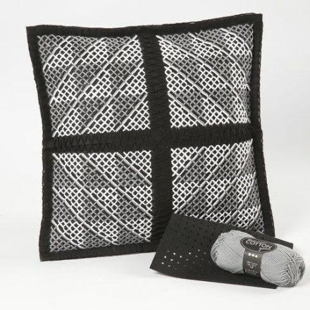 Un coussin avec le dessin d'une croix et un  motif au tricot