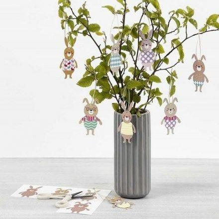 Des lapins de Pâques comme décorations à suspendre avec des habits faits dans du papier cartonné à motifs