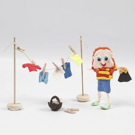 Une figurine en pâte Silk Clay et un étendoir en bois avec des habits en pâte Silk Clay