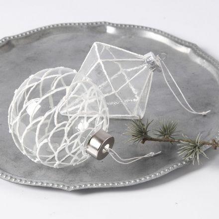 Des décorations en verre à suspendre, décorées d'un effet neige en 3D
