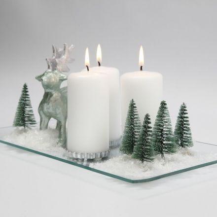 Une décoration de Noël avec de bougies, des rennes, des arbres et de la neige sur un plat en verre