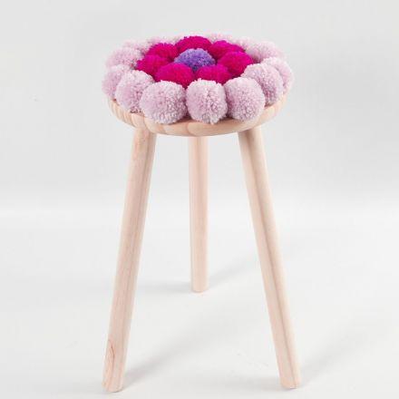Un coussin pour chaise décoré de pompons