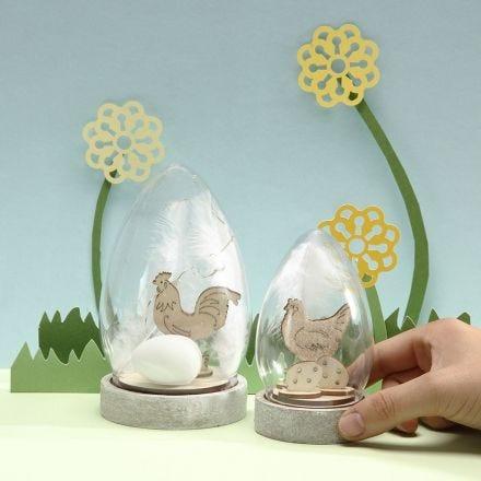Une cloche en verre décorée avec une figurine de Pâques à assembler, des oeufs et des plumes blanches