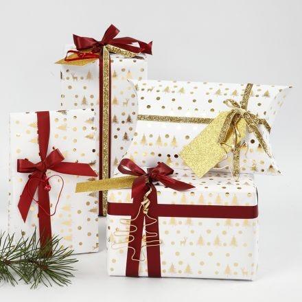 Papier cadeau de Noël blanc et doré décoré avec du ruban et des formes en fil bonsaï