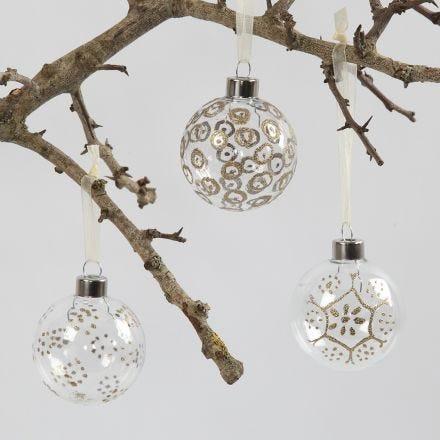 Des boules de verre décorées à l'aide d'un feutre à colle et de poudre à embausser