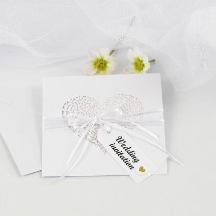 Une invitation de mariage avec un ruban de satin et une étiquette cadeau décorée d'autocollants gonflés