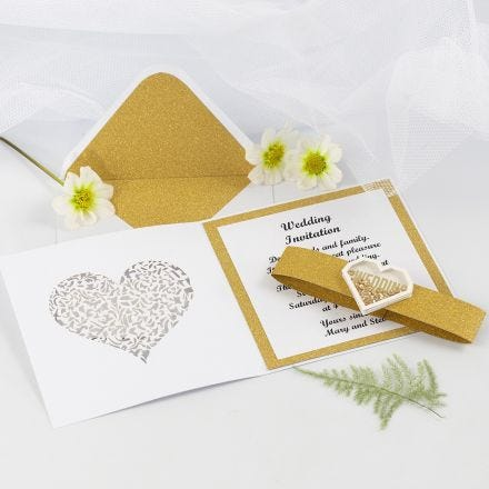 Une invitation de mariage faite avec du papier design doré à paillettes et un autocollant à secouer en forme de coeur