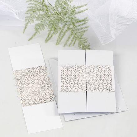 Une ceinture de papier cartonné à motif de dentelle en guise d'attache pour une carte de voeux pliée en trois