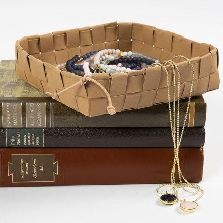 Un panier tressé avec des bandes de papier imitation cuir et sécurisé avec un cordon en cuir