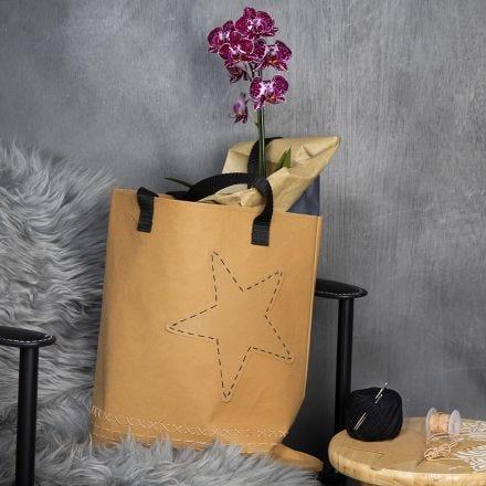 Un sac en papier imitation cuir avec un bord brodé et une étoile