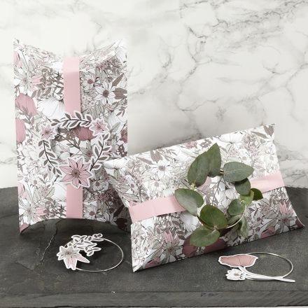 Boîtes cadeaux à plier, décorées avec un ruban rose, un anneau métallique et des découpes de fleurs en papier cartonné