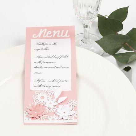 Une carte de menu décorée de papier cartonné à motif dentelle et de fleurs poinçonnées