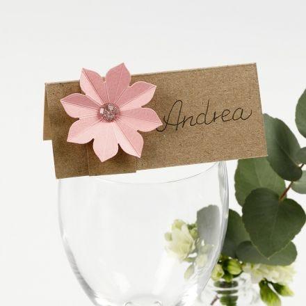 Un marque-place décoré avec une fleur en papier cartonné effet 3D