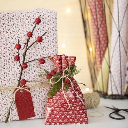 Emballage cadeau de Noël avec une brindille et de fausses baies
