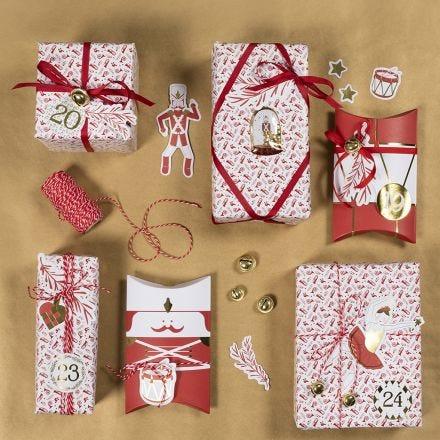 Du papier cadeau de Noël avec des autocollants casse-noisette et des motifs découpés dans du papier cartonné