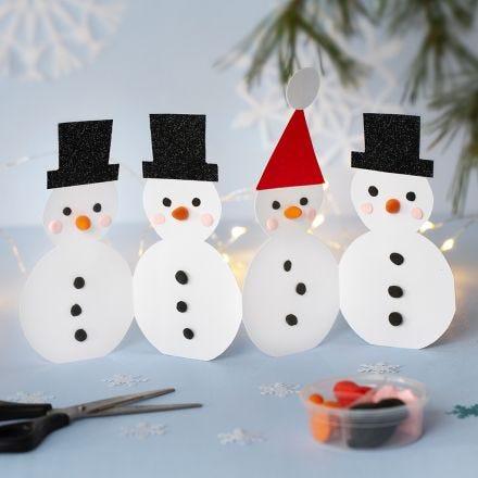 Une guirlande de  bonhommes de neige en papier cartonné, décorés avec de la pâte Silk Clay