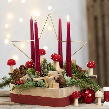Une couronne de l'Avent décorée d'une étoile métallique, de crapauds, d'épinettes, de pommes de pin et de bouts de bois