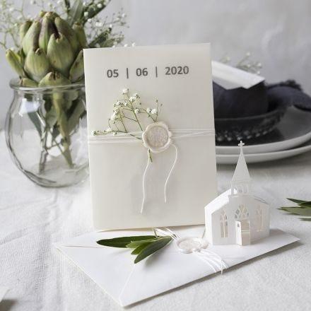 Une invitation dans des tons blanc cassé avec une église perforée et du papier vélin