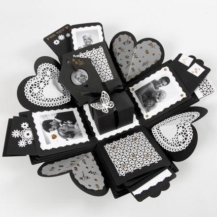 Une boîte à explosion avec des pochettes pour contenir des cartes et des photos
