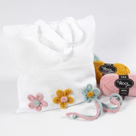 Un sac à provisions décoré de fleurs faites en tube tricoté