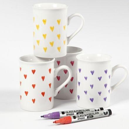 Des tasses en pocelaine decorées de coeurs à l'aide de feutres pour verre et porcelaine