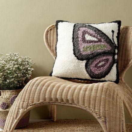 Un coussin décoré d'un papillon tracé au poinçon à broderie