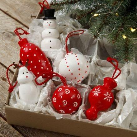 Des figurines en bois et des boules de Noël en bois à suspendre, décorées avec de la peinture acrilyque