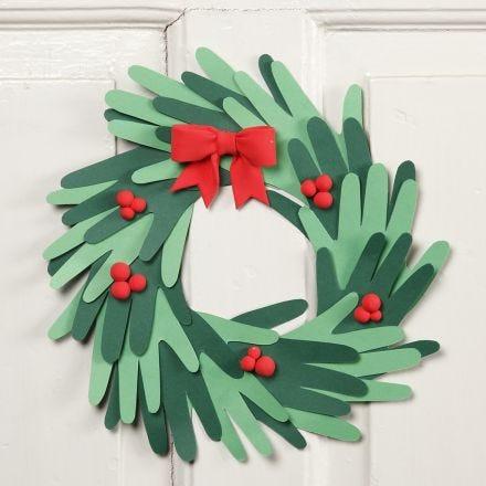 Une couronne de Noël faite avec des mains découpées dans du papier cartonné et des décorations en pâte Silk Clay