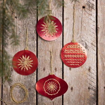 Des boules de Noël faites à partir de papier cartonné perforé, brodé de fil doré