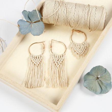 Des boucles d'oreilles créoles décorées d'un pendentif en macramé