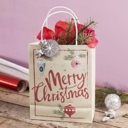 Un sac cadeau avec un motif de Noël, décoré avec une étoile, une guirlande et du papier de soie