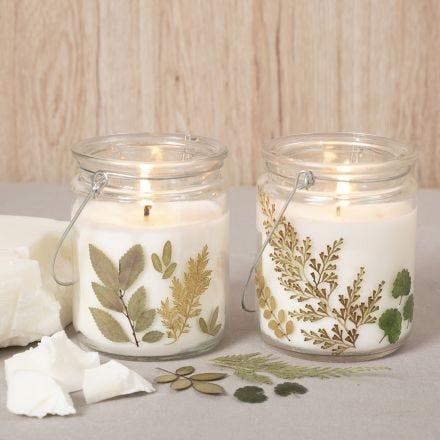 Des bougies en cire de colza dans une lanterne en verre décorée de fleurs séchées