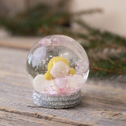 Une boule à neige avec un ange fait en pâte Fimo