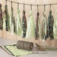 Une guirlande en cordon pour macramé, décorée de pompons en tissu