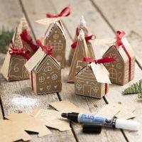 Un calendrier de l'Avent composé de 24 petites maisons et arbres en papier mâché