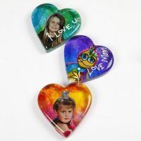 Un coeur en verre décoré avec une image et de la peinture pour verre