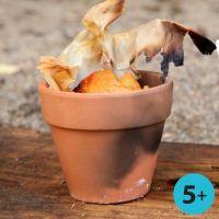 Pain fait sur feu dans un pot de fleurs en terre cuite rouge à bordure
