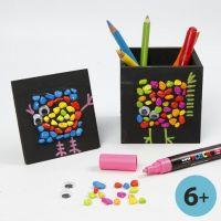 Un pot à stylos et un cadre avec collages peints en noir avec mosaïques et graphiques
