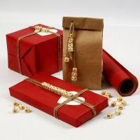 Emballage cadeau avec un petit mot avec des perles en forme de lettres en bois sur un bout de chanvre naturel