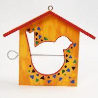 Une mangeoire pour oiseaux en forme de maison, peinte et décorée de motifs