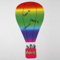 Une montgolfière faite de papier cartonné arc-en-ciel et d'un panier en carton ondulé