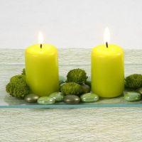 Des bougies vert citron et des pierres décoratives en verre sur un plat en verre